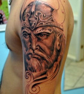 Angry vikings face tattoo on arm