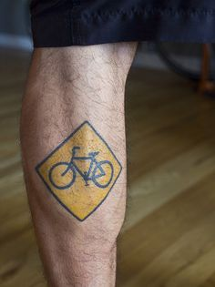 Bicycle sign tattoo on leg