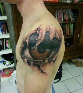 Big brown eye and skull tattoo on shoulder