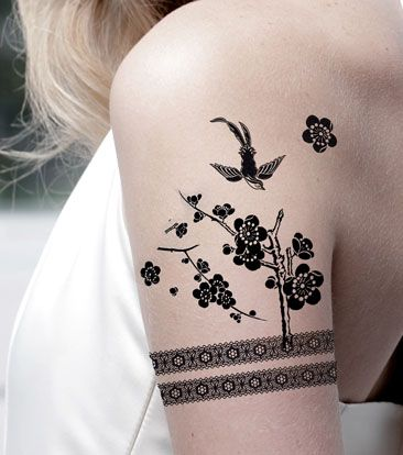 Birds, trees, flowers and black lace tattoo on arm