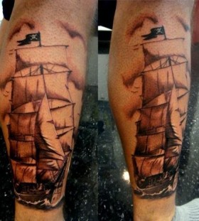 Black and white pirate ship tattoo on leg