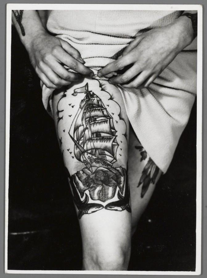 Black and white ship tattoo on leg