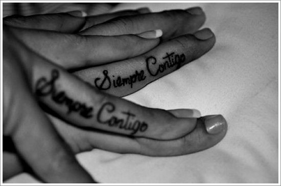 Black and white style quote tattoo on finger