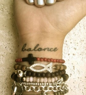 Black balance quote tattoo on arm