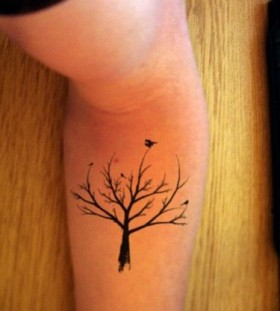 Black bird and tree tattoo on arm