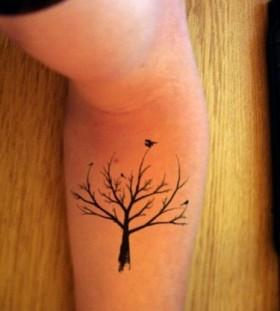 Black bird and tree tattoo on arm