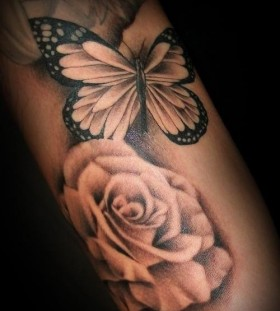 Black butterfly and rose tattoo on arm