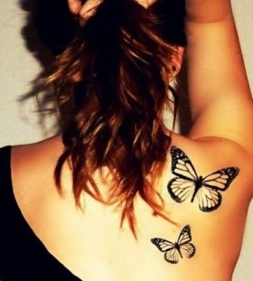 Black butterfly tattoo on shoulder