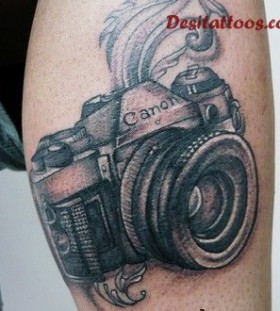 Black canon camera tattoo on leg