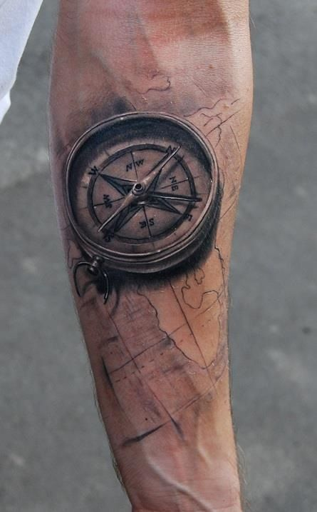 Black compass and map tattoo on arm