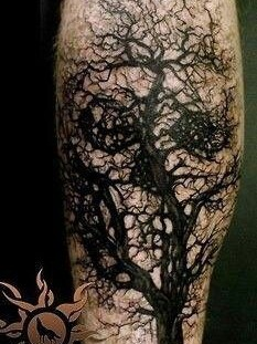 Black eyes and tree tattoo on leg