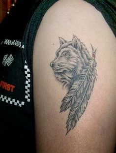 Black feather and wolf tattoo on arm