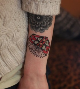 Black flower and book tattoo on arm