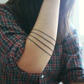 Black funny line tattoo on arm