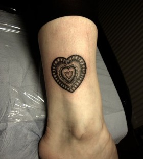 Black heart lace tattoo on leg