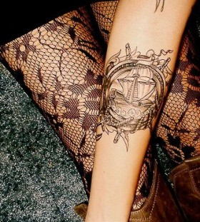 Black lace and ship tattoo on arm