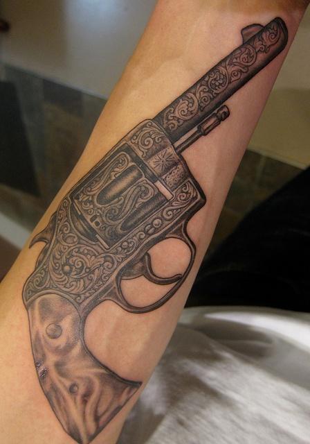 Black ornaments and gun tattoo