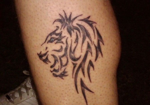 Black ornaments of lion tattoo on leg