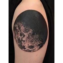 Black owal moon tattoo on shoulder