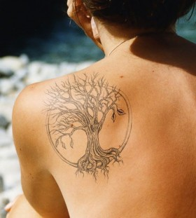 Black owal tree tattoo on shoulder