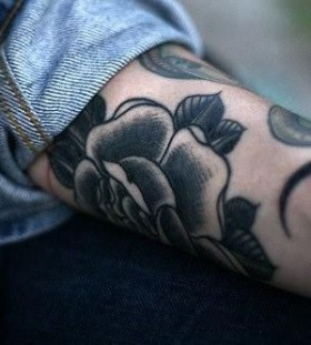 Black rose and moon tattoo on arm