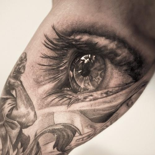 Black sculpture and eye tattoo on arm