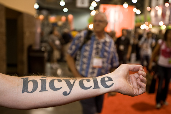 Black simple bicycle tattoo on arm