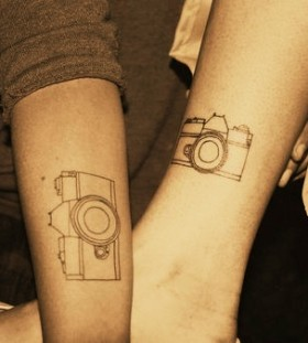 Black sketch camera tattoo on arm