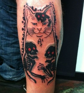 Black skull and cat tattoo on leg
