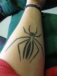 Black spider tattoo on arm