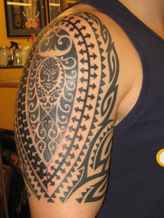 Black sun tribal tattoos on arm