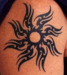 Black tribal sun tattoo on shoulder