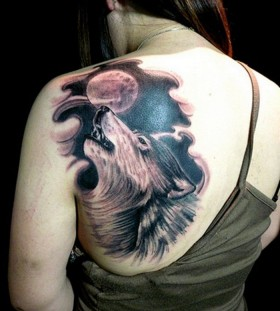 Black wolf and moon tattoo on shoulder
