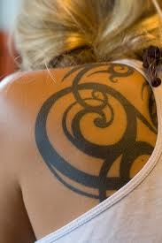Blonde girl tribal tattoo on shoulder