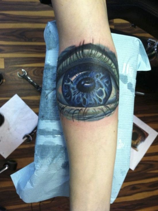 Blue and black eye tattoo on arm