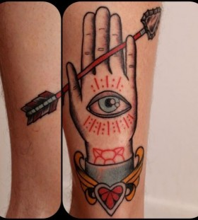 Blue and red palm eye tattoo on leg