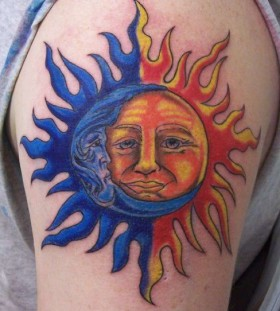 Blue and yellow moon tattoo on arm