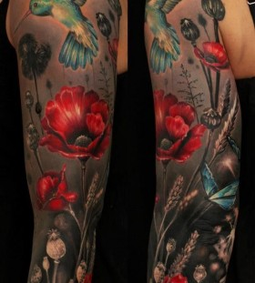 Blue bird and poppy tattoo on arm