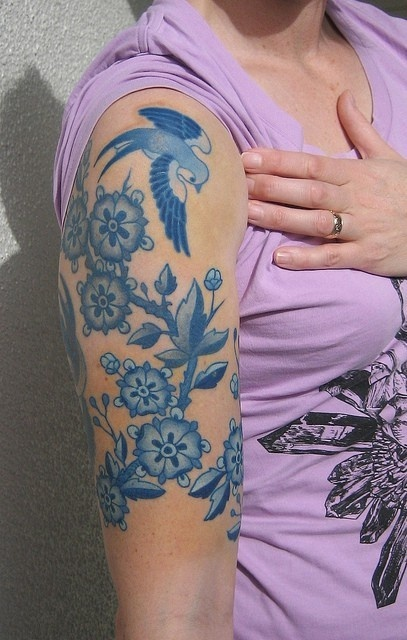 Blue flowers and birds tattoo on arm