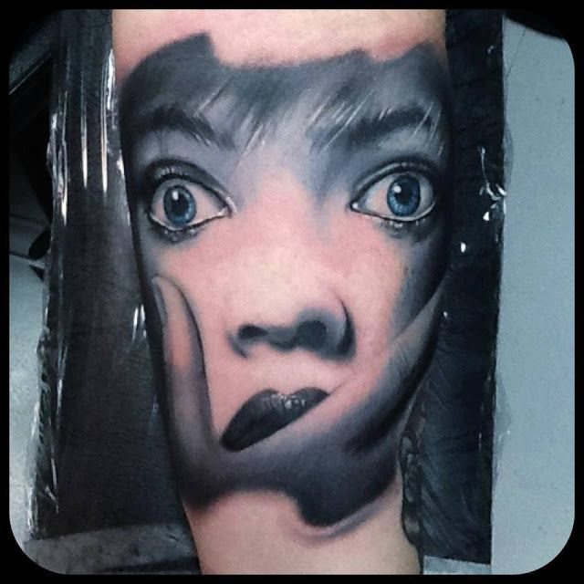 Blue hair face tattoo on arm