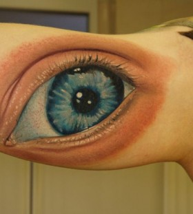 Blue men's eye tattoo on arm