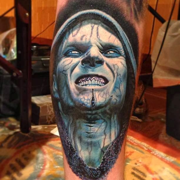 Blue men's face tattoo on leg