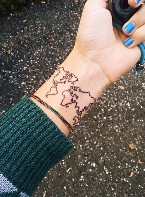 Blue nails and map tattoo on arm