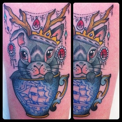 Blue ship, cup and rabbit tattoo on arm