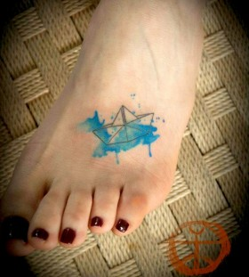 Blue ship origami tattoo on leg