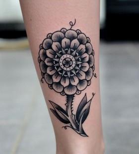 Bright black flower tattoo on leg
