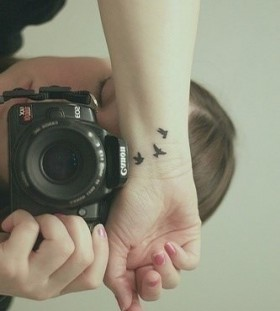 Canon camera and black bird tattoo on arm