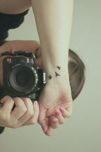Canon camera and black bird tattoo on arm