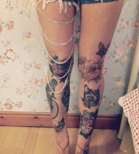 Cat, bike and red rose tattoo on leg