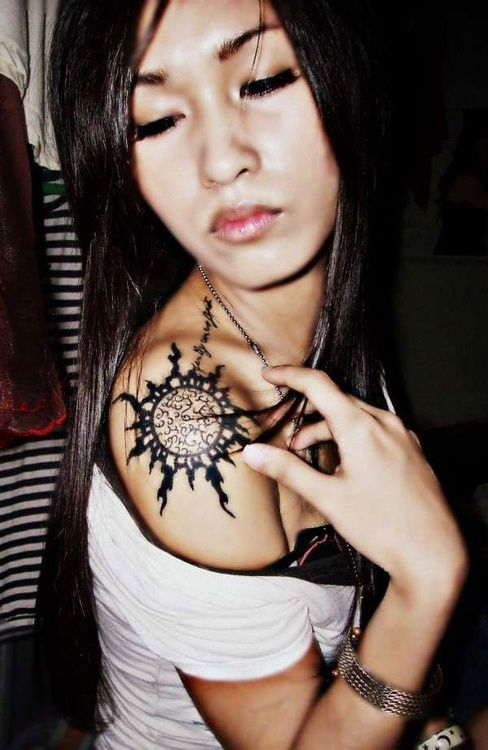 Chinese girl's sun tattoo on shoulder